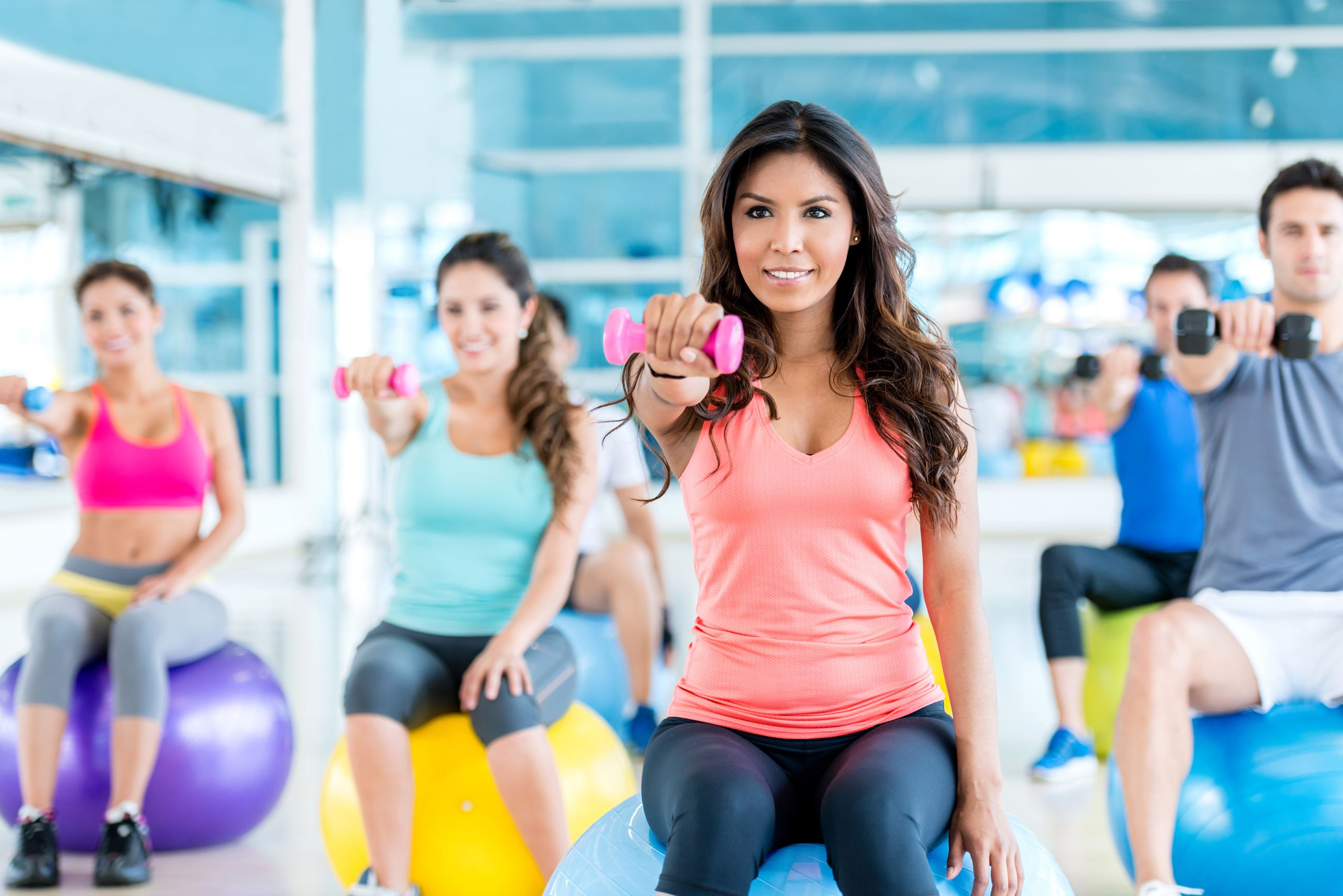 Woman leading fitness class with weight on exercise ball