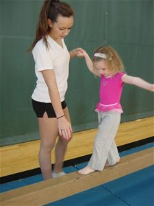 Girl Walking on a Balance Beam with Assistance from a Woman
