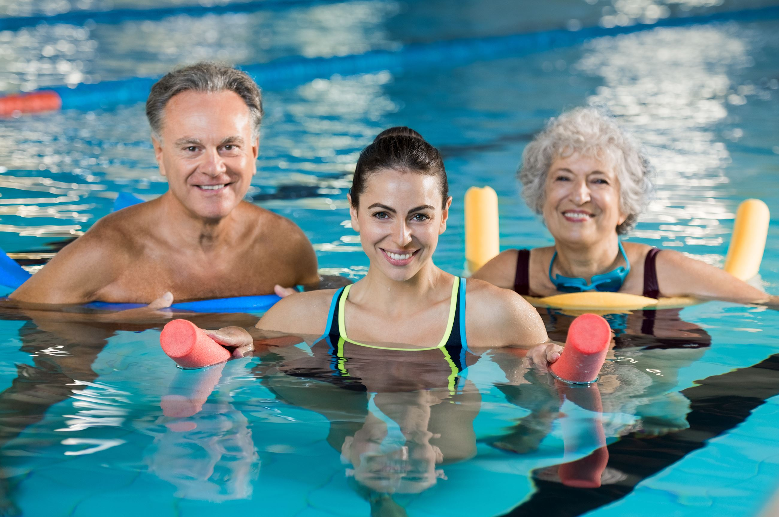 Group of seniors and adult in water doing water aerobics